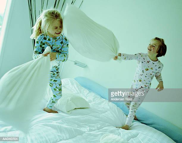 Two girls (6-8) having pillow fight on bed (blurred motion)
