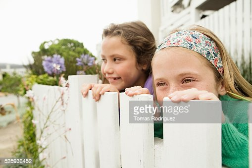 Two girls (6-7), (8-9) hiding behind fence : Stock-Foto