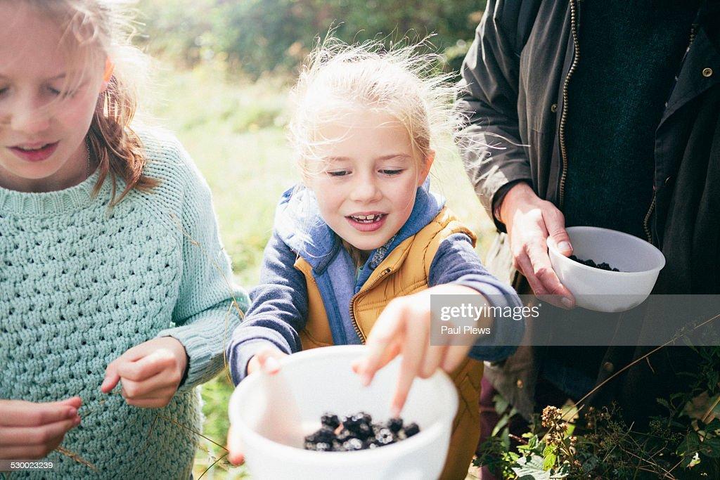 Two girls holding blackberries in bowl