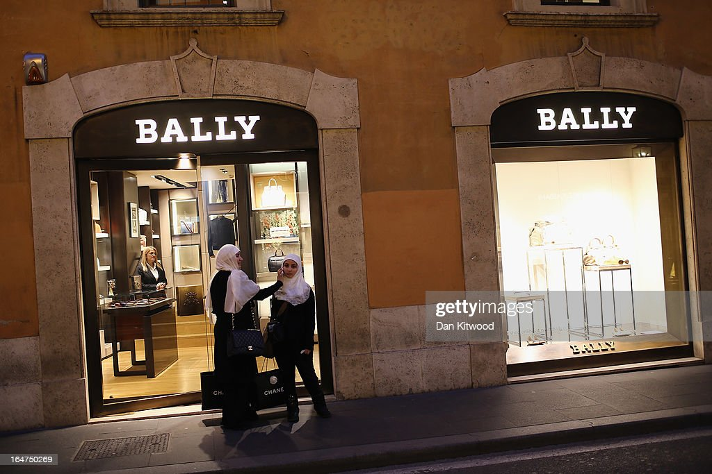 Two girls holding Chanel shopping bags walk through the fashionable Via Condotti shopping area near the Spanish Steps on March 27, 2013 in Rome, Italy.