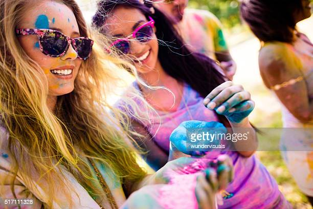 Two Girls Holding Colorful Powder at Holi Festival