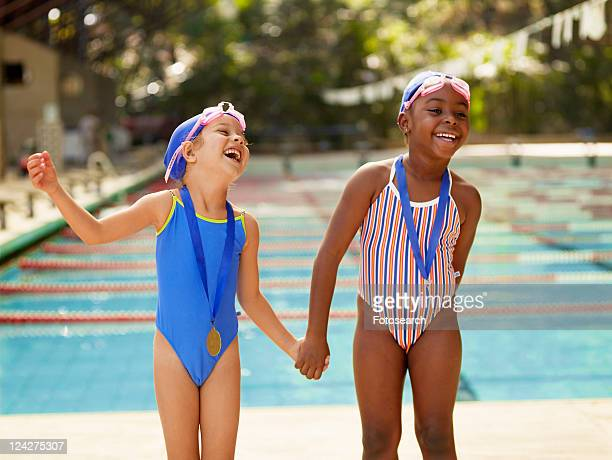 Two girls holding hands by swimming pool