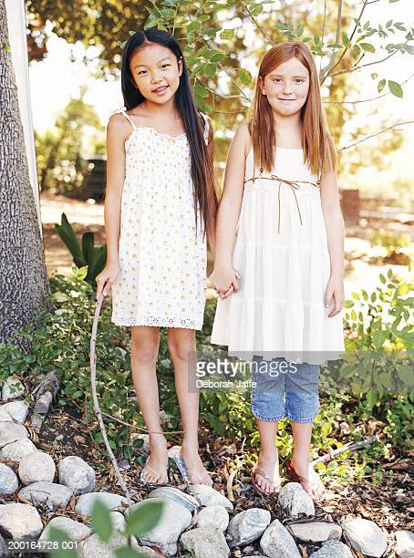 Two girls (8-10) holding hands in park, portrait