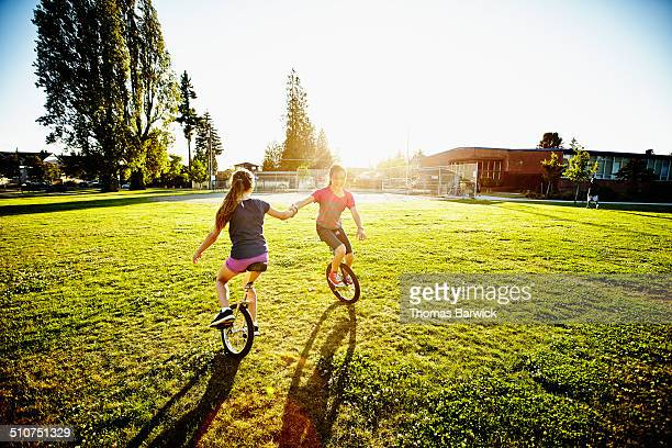 Two girls holding hands riding unicycles in circle