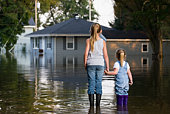 Two girls holding hands, watching during flood