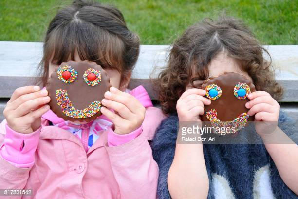 Two girls holding smiley cookies over their face