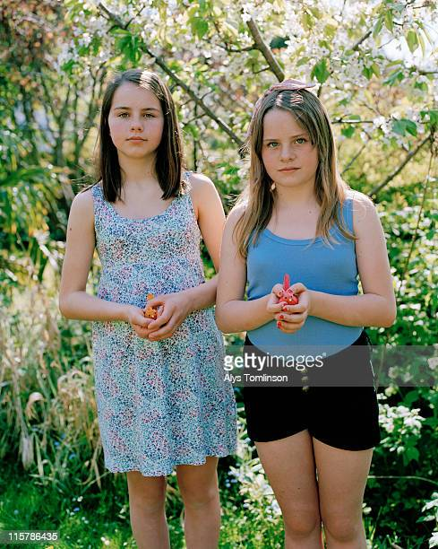 Two Girls Holding Toy Birds in a Garden