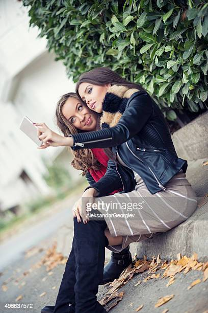 Two Girls how sitting on City Street and Taking Selfie
