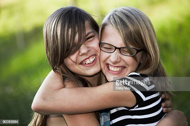 Two girls hugging, laughing