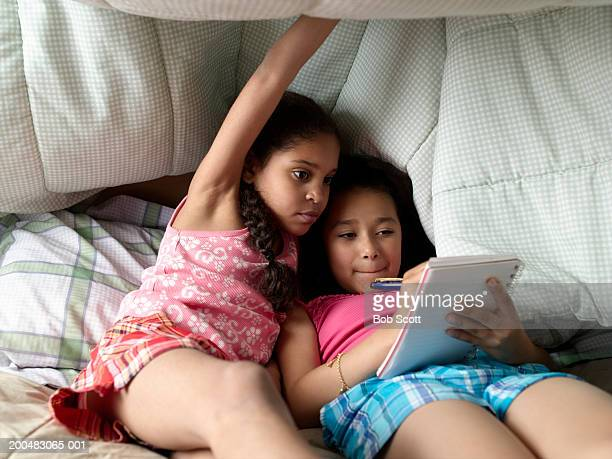 Two girls (8-10) in bed, one writing note