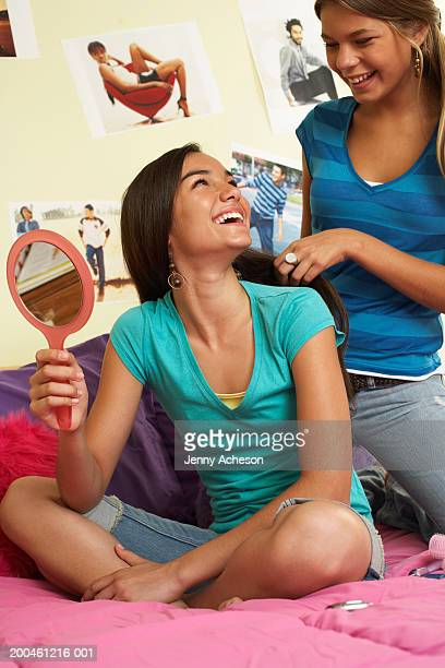 Two girls (13-15) in bedroom, one doing other's hair, smiling