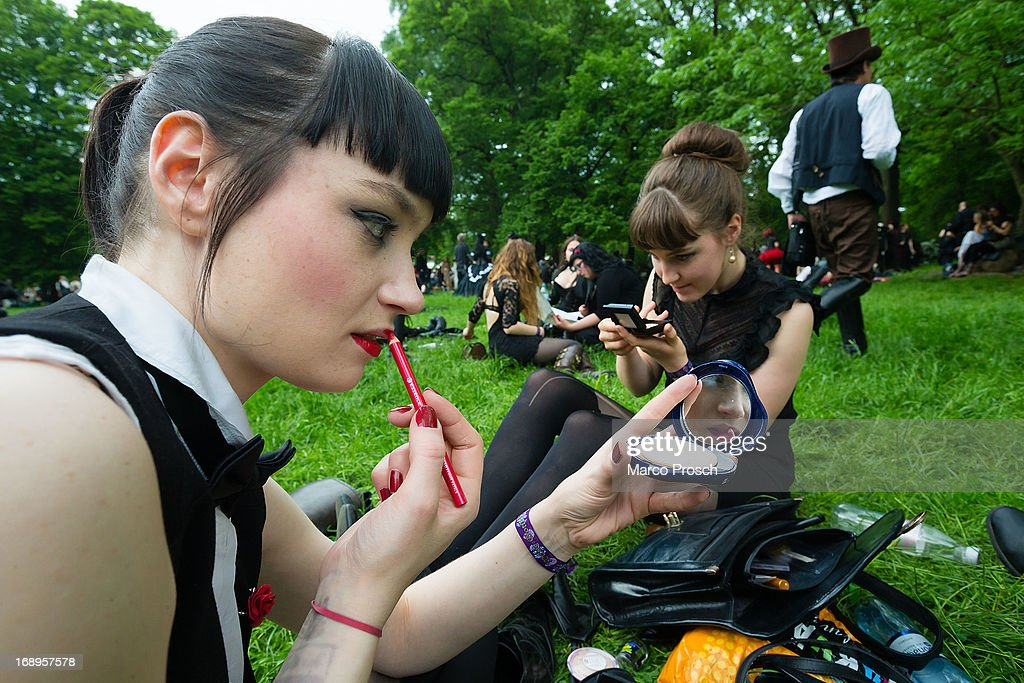 Two girls in black clothing refresh their make-up during the traditional park picnic on the first day of the annual Wave-Gotik Treffen, or Wave and Goth Festival, on May 17, 2013 in Leipzig, Germany. The four-day festival, in which elaborate fashion is a must, brings together over 20,000 Wave, Goth and steam punk enthusiasts from all over the world for concerts, readings, films, a Middle Ages market and workshops.