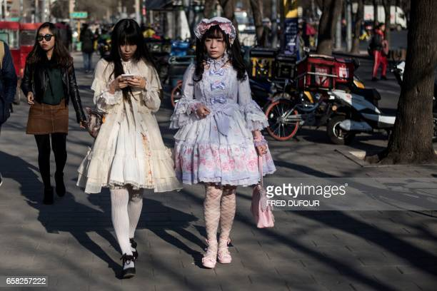 TOPSHOT Two girls in cosplay dresses walk in the street in Beijing on March 27 2017 / AFP PHOTO / FRED DUFOUR