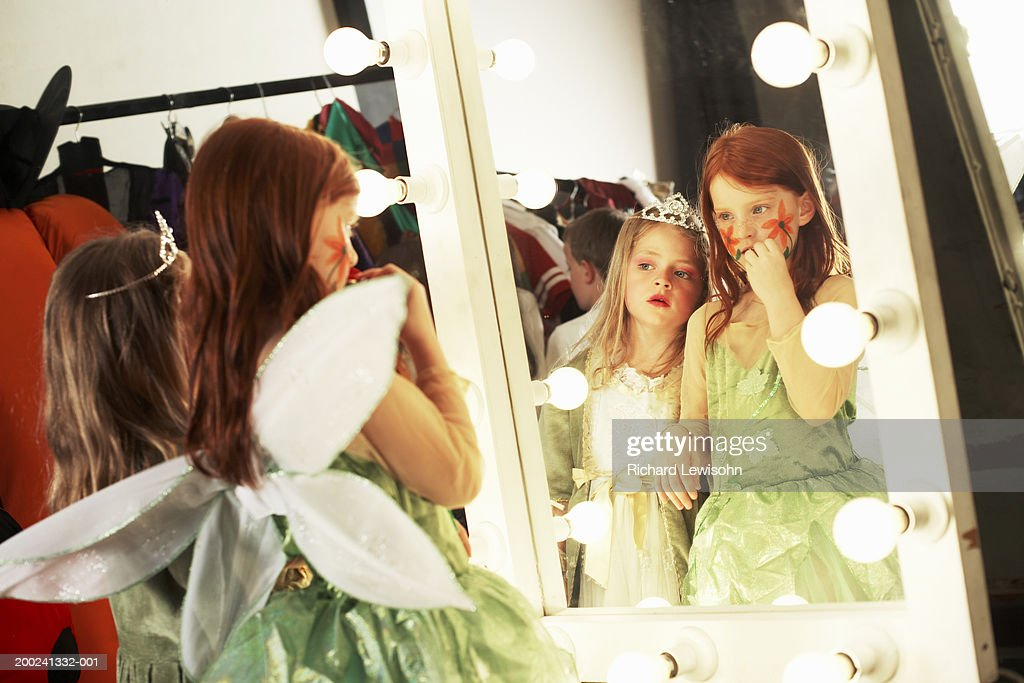 Two girls (5-8) in costumes looking at reflections in backstage mirror : Stock Photo