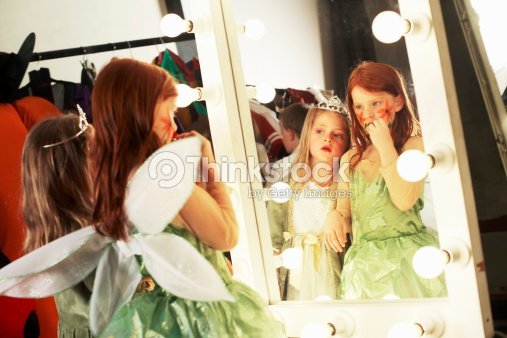 Two Girls In Costumes Looking At Reflections In Backstage Mirror