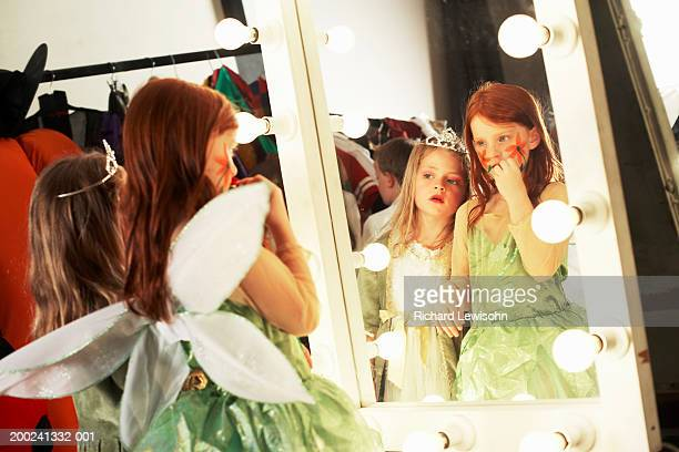 Two girls (5-8) in costumes looking at reflections in backstage mirror