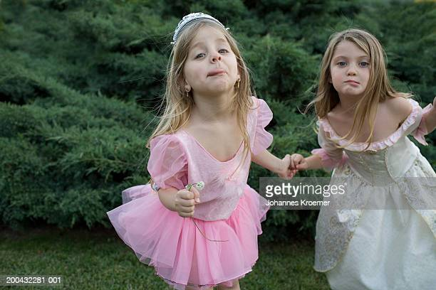 Two girls (4-6) in costumes making faces in backyard, portrait