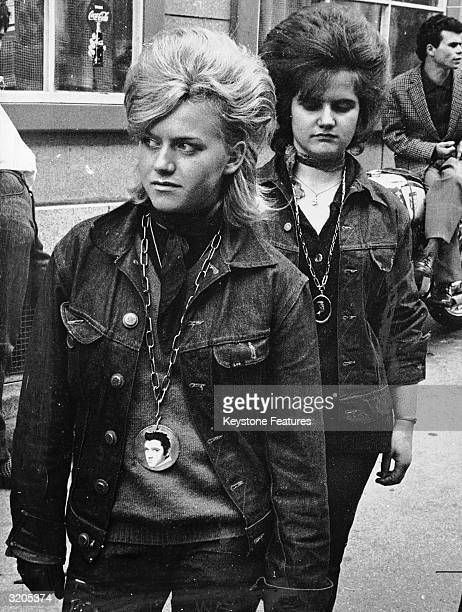 Two girls in denim jackets bouffon hairstyles and large Elvis Presley medallions attend a Teddy Boy convention in Zurich