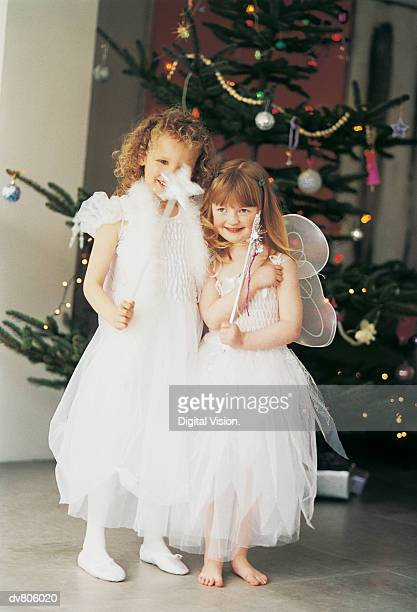 Two Girls in Fairy Costume Standing by a Christmas Tree