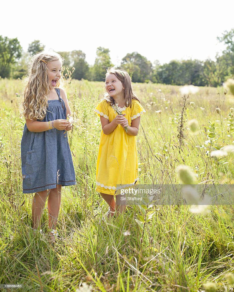 Two girls in field laughing together : Stock Photo