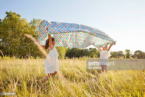 Two girls in field lifting sheet their overheads
