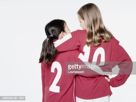 Two girls (8-11) in football strips, arms around each other, rear view : Stock Photo