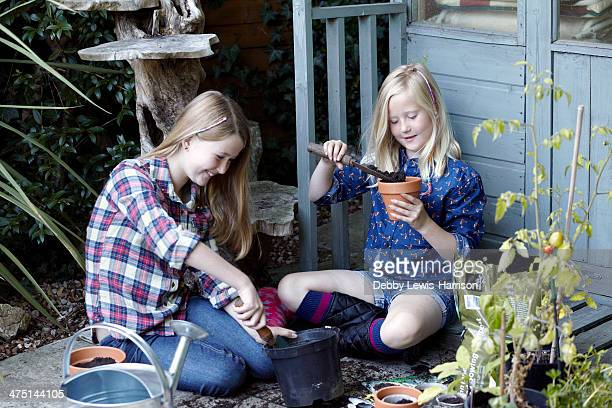 Two girls in garden planting seeds into pots