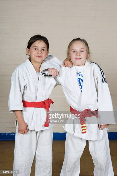 Two girls in  Judo kit posing for the camera.