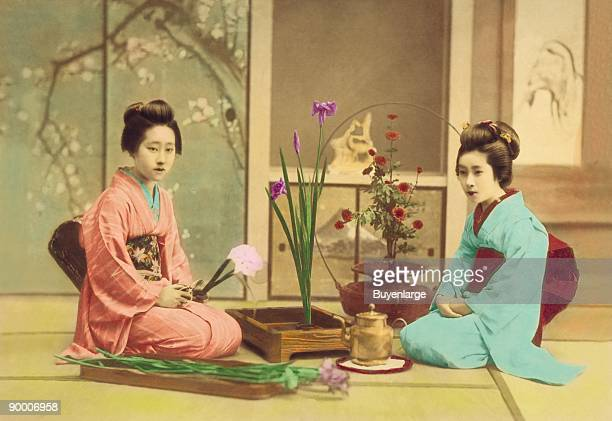 Two girls in kimono obe and sashes arrange flowers as Ikibana in the Japanese Tradition