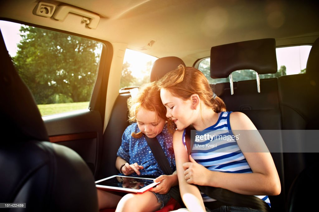 Two girls in rear seat of car : Stock Photo