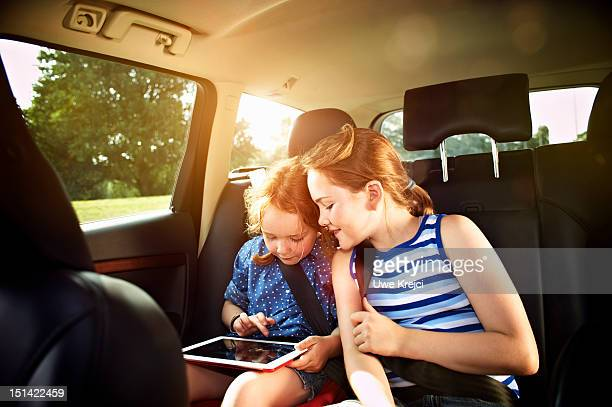 Two girls in rear seat of car