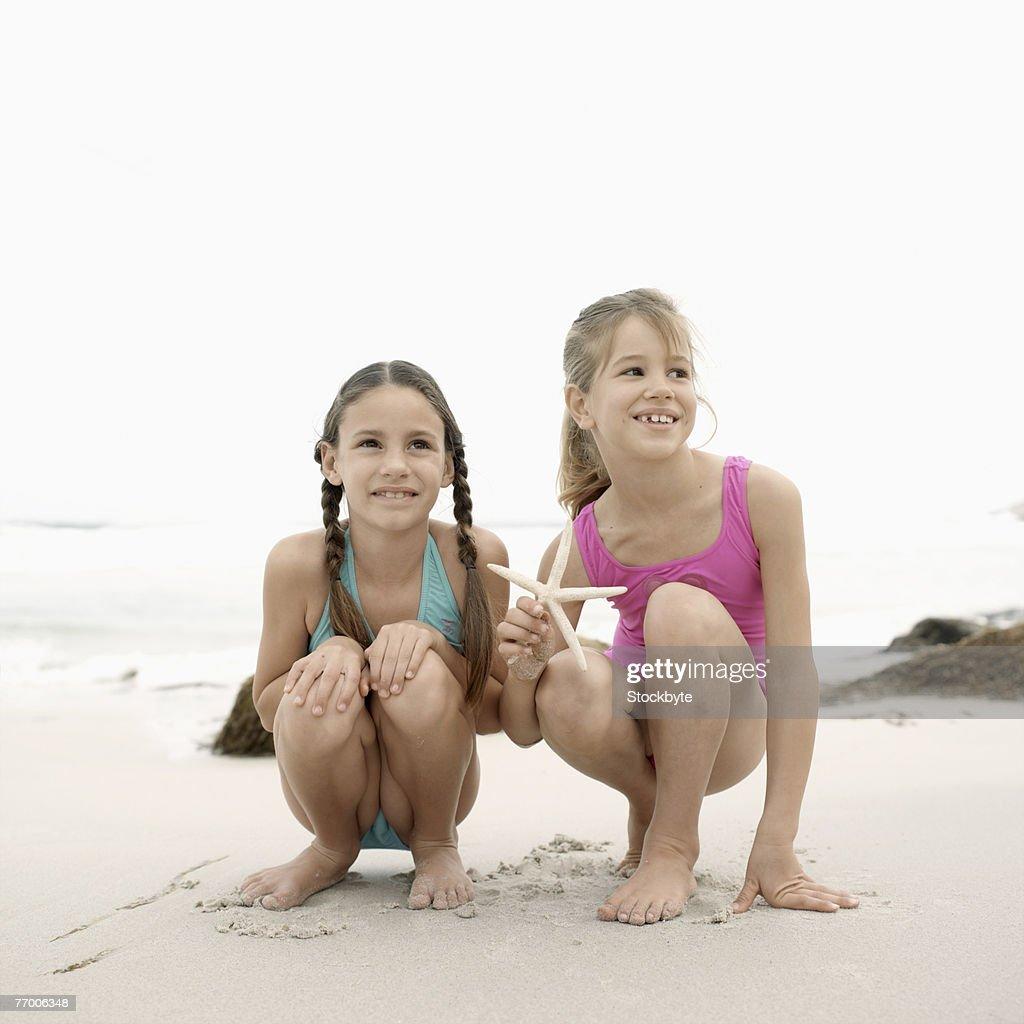 two girls in swimwear crouching on beach picture id77006348?s=170667a&w=1007 two girls in swimwear crouching on beach stock photo thinkstock,9 10 Swimwear