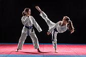 Two girls in taekwondo combat practicing martial arts. They wears kimonos