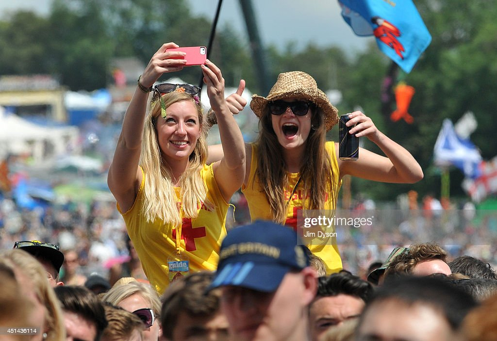 Two girls in the crowd take a selfie as they watch The 1975 perform on the Pyramid stage during day three of the Glastonbury Festival at Worthy Farm...