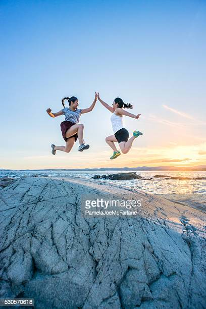 Two Girls Jumping and Giving High Fives on Rocky Beach
