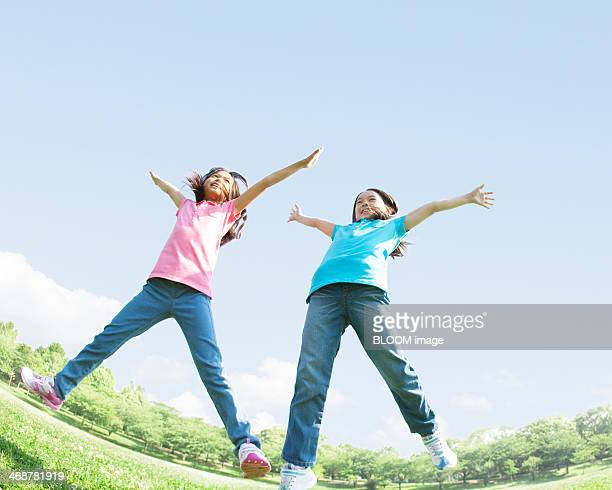 Two Girls Jumping In Park
