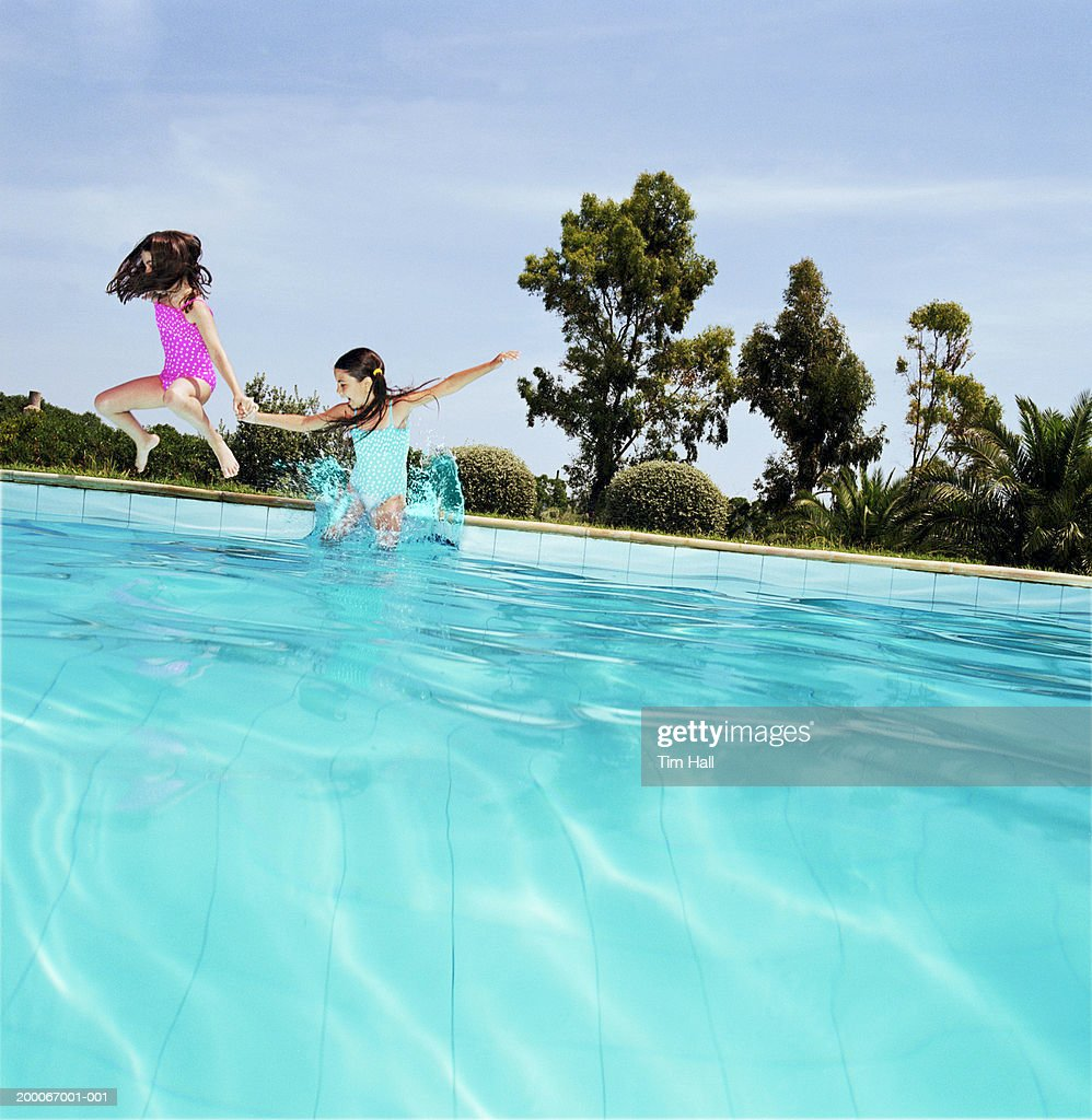 Two Girls Jumping Into Swimming Pool Stock Photo Getty Images
