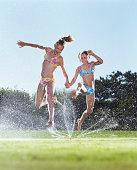 Two girls (9-12) jumping over sprinkler, holding hands