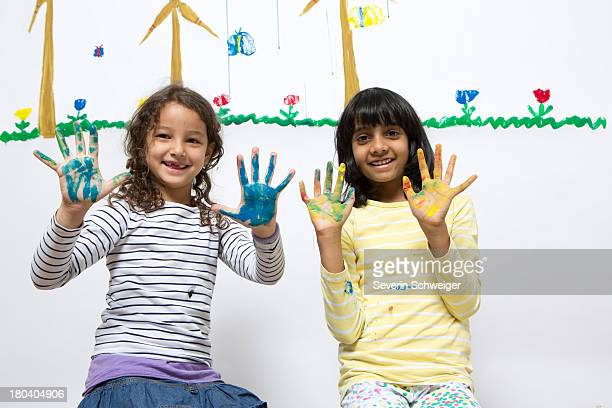 Two girls kneeling on floor with painted hands