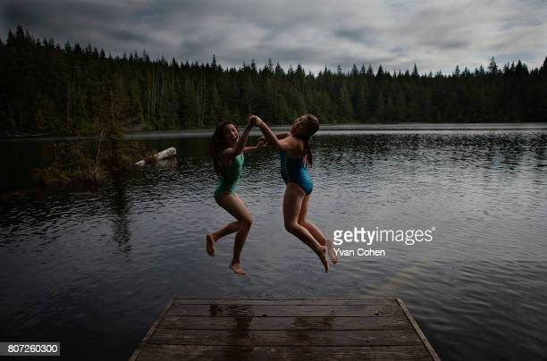 Two girls laugh as a jump into Lizard lake on Vancouver Island in the province of British Columbia in Canada