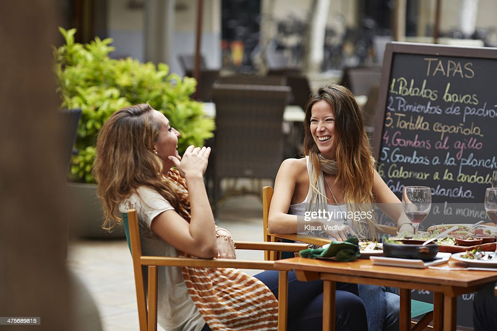 Two girls laughing together at restaurant