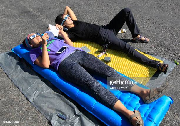 Two girls lay on the ground as they view the solar eclipse in the first phase of a total eclipse in Grand Teton National Park on August 21 2017...