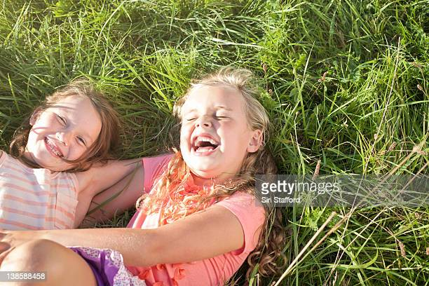 Two girls laying in grass laughing