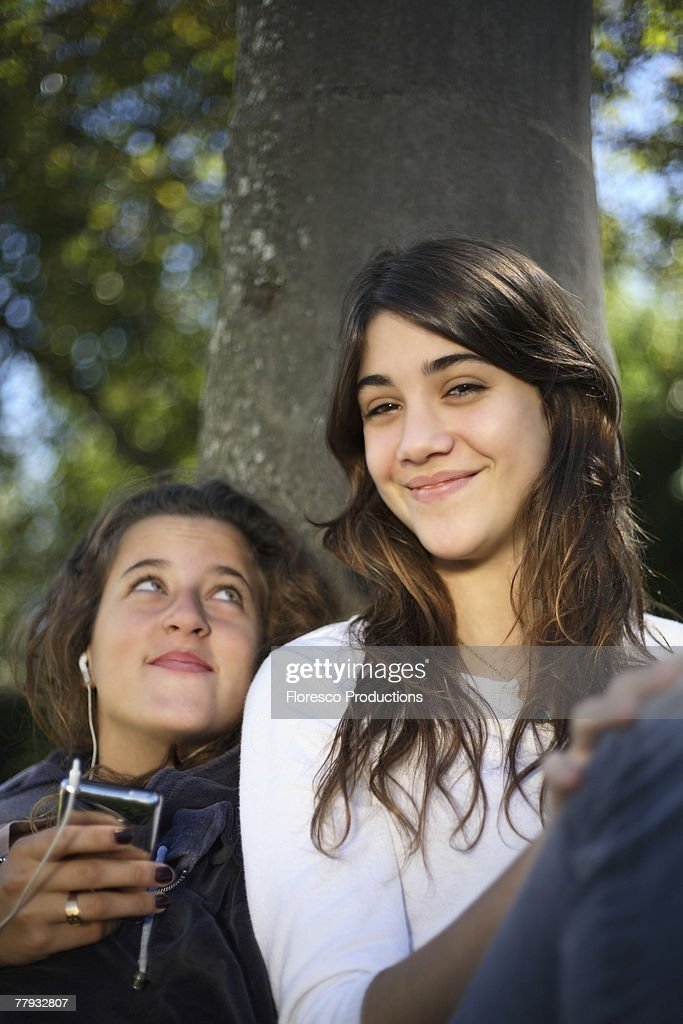 Two girls leaning against a tree with an MP3 Player : Stock Photo