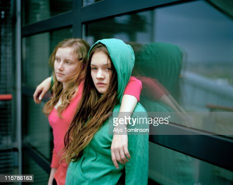 Two Girls Leaning Against a Window : Stock Photo