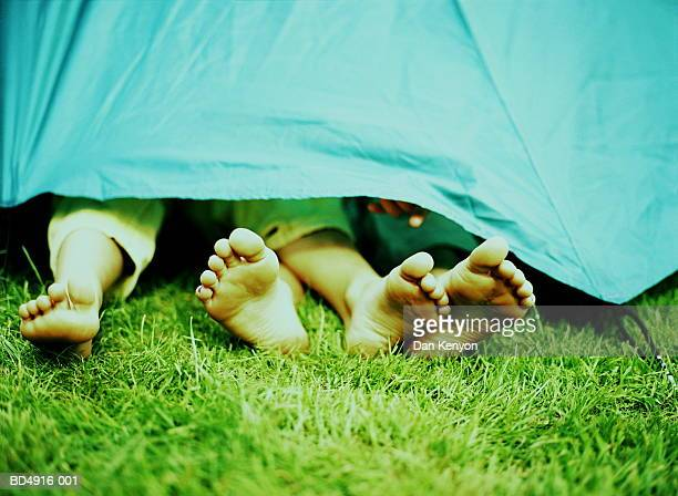 Two girls' legs protruding from tent
