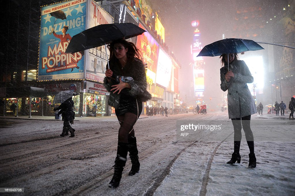 Two girls look for a taxi in the snow in Times Square in New York on February 8, 2013 during a storm affecting the northeast US. The storm was forecast to bring the heaviest snow to the densely-populated northeast corridor so far this winter, threatening power and transport links for tens of millions of people and the major cities of Boston and New York. New York and other regional airports saw more than 4,500 cancellations ahead of what the National Weather Service called 'a major winter storm with blizzard conditions' along most of the region's coastline. AFP PHOTO / MEHDI TAAMALLAH
