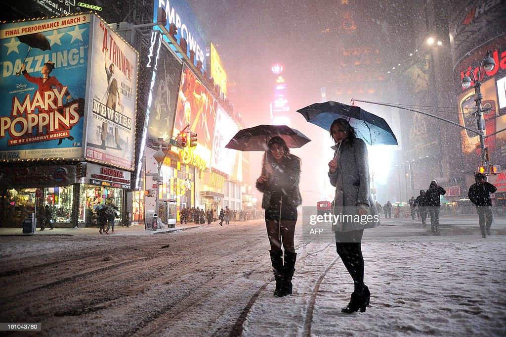 Two girls look for a taxi in the snow in Times Square in New York on February 8, 2013 during a storm affecting the northeast US. The storm was forecast to bring the heaviest snow to the densely-populated northeast corridor so far this winter, threatening power and transport links for tens of millions of people and the major cities of Boston and New York. New York and other regional airports saw more than 4,500 cancellations ahead of what the National Weather Service called 'a major winter storm with blizzard conditions' along most of the region's coastline.