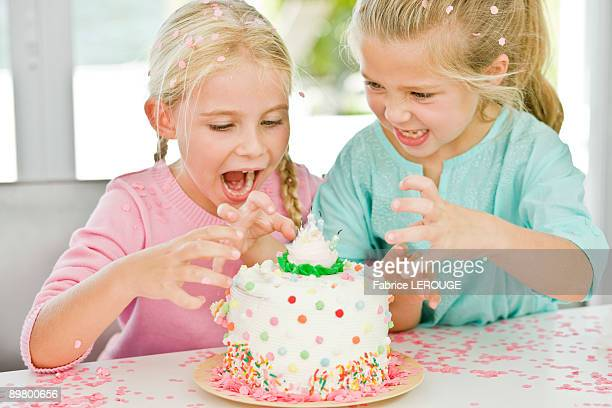 Two girls looking at a birthday cake