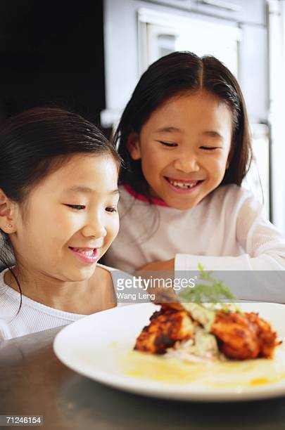 Two girls looking at a plate of food, smiling
